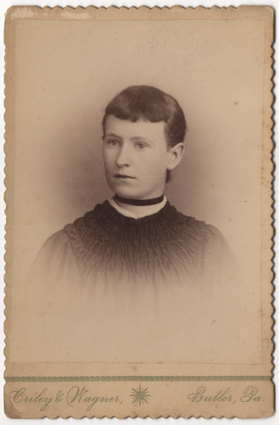A short haired young woman with dark straight hair parted on the left. She is wearing a dress and does not have pierced ears. She wears a ribbon around her throat like a choker.