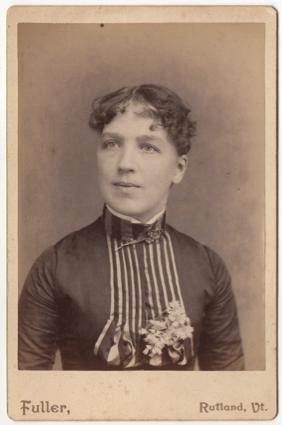 A woman with short dark curly hair. She is wearing a dress with pleats down the front and flowers on her chest. She has a high collar with a broach or clasp at her throat.