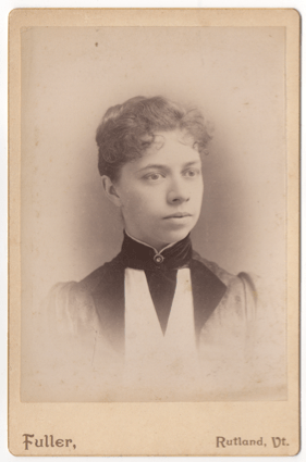 A woman with short or pulled back curly hair wearing a dress with a high collar and a clasp with a stone in the center. Her dress has large lapels.