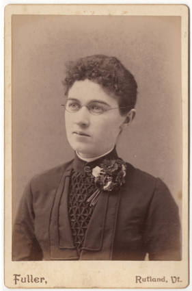 A young woman in a dark dress or top. The front has an intricate cloth lattice in a triangular pattern. He has a corsage and a clasp at the front of her collar. She is wearing glasses and has short curly hair or it is pulled back.