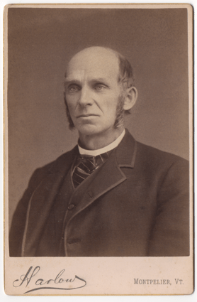 A bald older gentleman with log sideburns. He is wearing a suit coat with a matching undervest. He wears a tie and has a round collar that could possibly denote clergy.