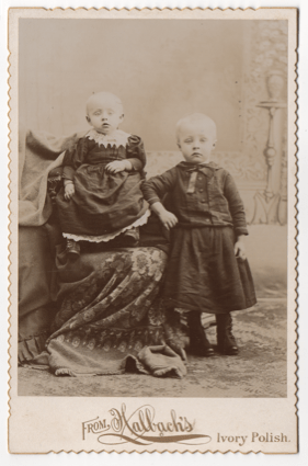 Two young tow headed children, both wearing dresses. Most likely two boys, but the infant could be either.