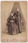 Two women. One seated, the other standing with her arm resting on the other's shoulder. Both wear full length dresses with one being a simpler…