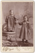 Two small children in matching dresses. One is standing in a chair, the other beside. The younger of the two appears to be a boy, the other a girl.…